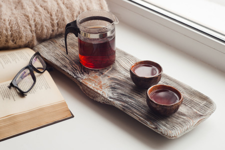 Photo for Still life details, cups of asian tea and teapot on vintage wooden tray on windowsill in living room. Lazy winter weekend with a book at home - Royalty Free Image