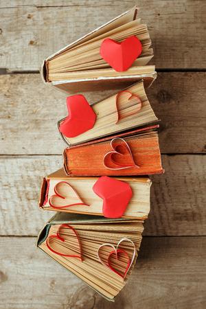 Foto de various old books and origami paper craft red heart on vintage wooden - Imagen libre de derechos