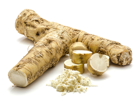 Foto de One whole, one half and freshly grated mash of horseradish root, isolated on white background, sliced circles  - Imagen libre de derechos