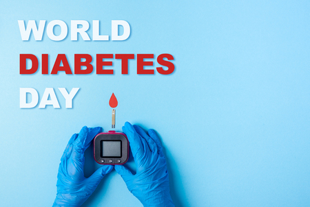 Foto per inscription world diabetes day and Nurse making a blood test with red blood drop with Blood glucose test strip and Glucose meter. Copy space. Top view - Immagine Royalty Free