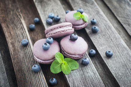 Photo for Violet french macarons with blueberry and mint on wooden table - Royalty Free Image