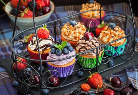 Photo pour Set of different delicious cupcakes on dark - image libre de droit