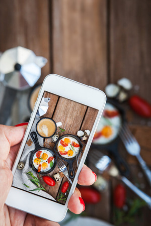 Photo pour Woman hands taking food photo of breakfast with fried eggs by mobile smart phone - image libre de droit