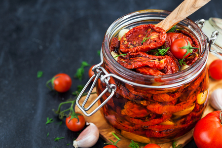 Photo for Sun dried tomatoes with garlic and olive oil in a jar on dark background - Royalty Free Image