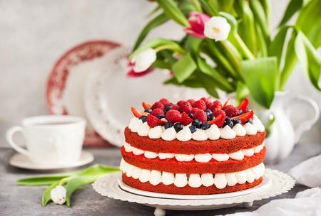 Foto de Delicious homemade red velvet cake decorated with cream and fresh berries - Imagen libre de derechos