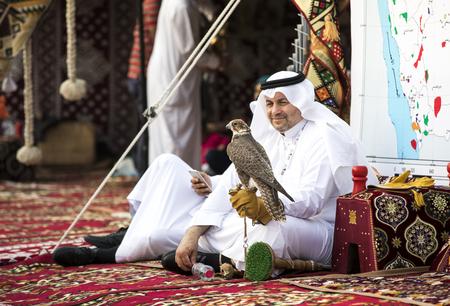 Photo pour Abu Dhabi, United Arab Emirates, December 8th, 2017: emirati man with his falcon at a Falconry festival - image libre de droit