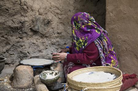 Foto de Al Hamra Oman, Febrary 2nd, 2018: omani woman making preparations in the kitchen of traditional house - Imagen libre de derechos