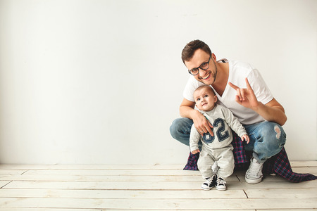 Foto de Young hipster father and cute baby boy sitting on rustic wooden floor over white  - Imagen libre de derechos