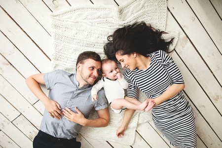 Foto de Happy young father mother and cute baby boy lying on rustic wooden floor - Imagen libre de derechos