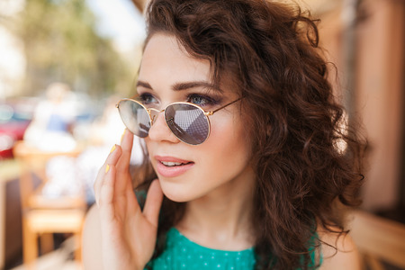 Photo pour Young beautiful woman in round sunglasses with curly hair with cocktail making an order at the terrace of cafe - image libre de droit