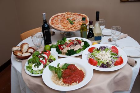beautiful table of italian salads, pasta, pizza and drinks