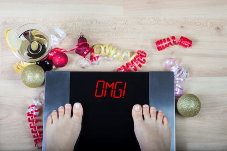 Foto de Digital scales with female feet on them and signomg! surrounded by Christmas decorations and glass of vermouth. Shows how alcohol and unhealthy lifestile during xmas holidays effect our body. - Imagen libre de derechos