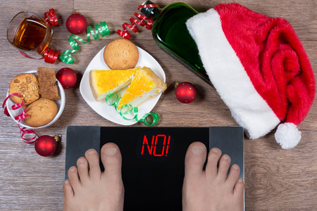 Foto de Digital scales with male feet on them and sign no! surrounded by Christmas decorations, sweets and bottle of alcohol. Shows how unhealthy lifestile during xmas holidays effects our body. Top view. - Imagen libre de derechos