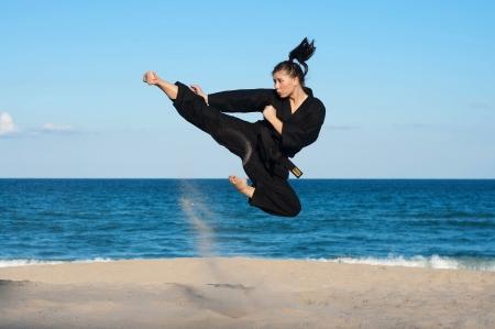 A female, fourth degree, Taekwondo black belt athlete performs a midair jumping kick on the beach