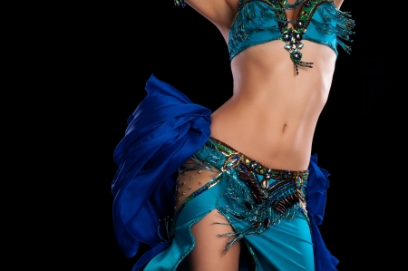Photo for Torso of a female belly dancer wearing a teal blue costume and shaking her hips  Isolated on a black background   - Royalty Free Image