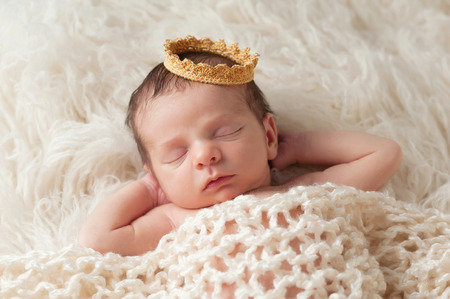 Photo pour Portrait of a 12 day old newborn baby boy wearing a gold crown  He is sleeping on a beige flokati rug with his hands behind his head  - image libre de droit