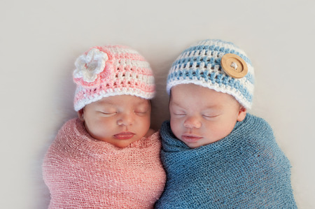 Photo pour Five week old sleeping boy and girl fraternal twin newborn babies  They are wearing crocheted pink and blue striped hats  - image libre de droit