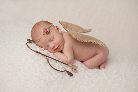 Photo for Portrait of a smiling, red headed, 2 week old, newborn baby girl  She is wearing a Cupid costume with angel wings, bow and arrow and is sleeping on a cream colored blanket  - Royalty Free Image