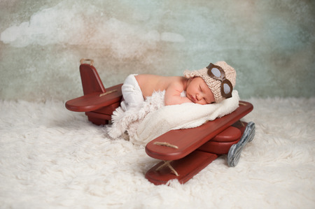 Photo pour Studio portrait of an eight day old newborn baby boy wearing an aviator cap with goggles. He is sleeping on a vintage inspired airplane posing prop. - image libre de droit