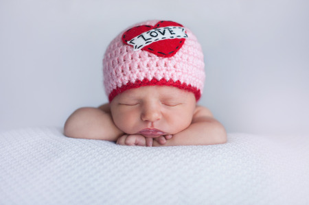 Foto de Portrait of a seven day old sleeping baby girl wearing a crocheted \Love\ beanie. Cute shot to use for Valentine - Imagen libre de derechos