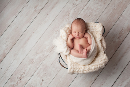 Photo pour A portrait of a seven day old, newborn baby sleeping in a wire basket on a whitewashed, wooden floor. - image libre de droit