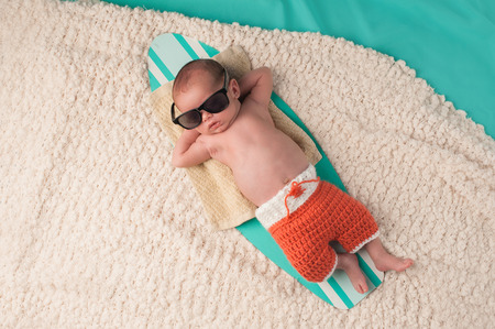 Photo pour Newborn baby boy sleeping on a tiny surfboard. He is wearing black sunglasses and crocheted boardshorts. - image libre de droit