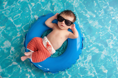 Photo for Three week old newborn baby boy sleeping on a tiny inflatable swim ring. He is wearing crocheted board shorts and black sunglasses. - Royalty Free Image