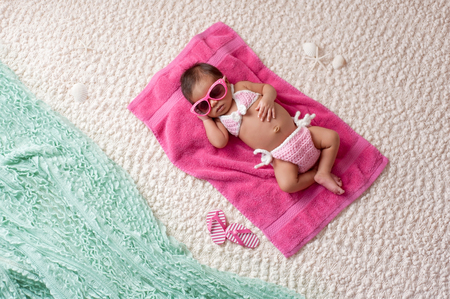 Four week old newborn baby girl sleeping on a pink towel. She is wearing a crocheted pink and white bikini and pink sunglasses. Shot in the studio with props made to look as if she's at a beach.