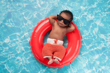 Foto de Two week old newborn baby boy sleeping on a tiny inflatable swim ring. He is wearing crocheted board shorts and black sunglasses. - Imagen libre de derechos