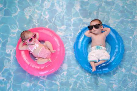 Photo pour Two month old twin baby sister and brother sleeping on tiny, inflatable, pink and blue swim rings. They are wearing crocheted swimsuits and sunglasses. - image libre de droit