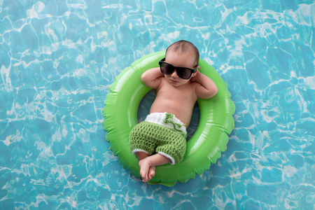 Photo for Two week old newborn baby boy sleeping on a tiny, green, inflatable swim ring. He is wearing green, crocheted board shorts and black sunglasses. - Royalty Free Image