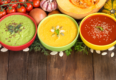 Three fresh soups in colorful bowls and vegetables on a wooden table