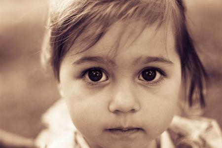 Foto de Portrait of a sad liitle girl close-up. Toned - Imagen libre de derechos