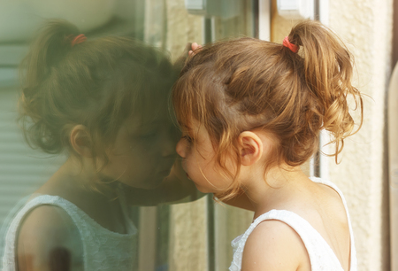 Photo for Thoughtful little girl looking through the window - Royalty Free Image