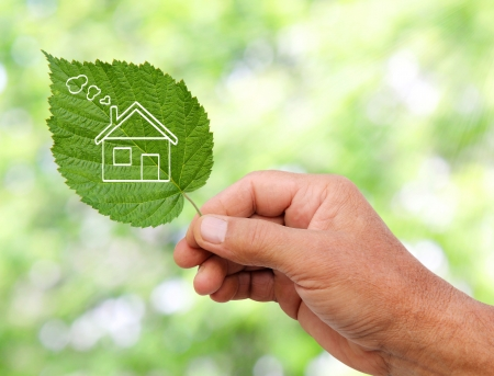 Photo pour Eco house concept, hand holding eco house icon in nature  - image libre de droit