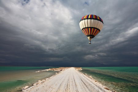 Photo for Picturesque bright balloon with a basket of passenger flying in a thunderstorm over the shoal Dead Sea  - Royalty Free Image