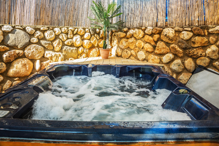 Photo for Bathtub -  jacuzzi in garden. Water in bathtub rages - Royalty Free Image