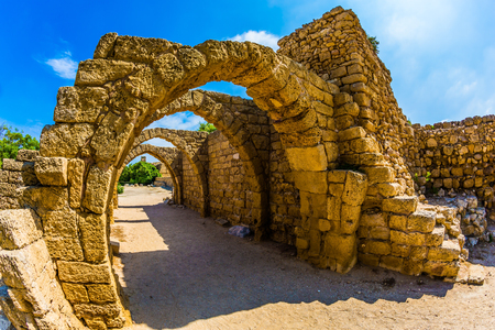 Foto de The remains of the covered arcades in ancient Caesarea. Excursion to the Archaeological Park of the Roman Empire. Sunny spring day. Israel. Concept of ecological and historical tourism - Imagen libre de derechos