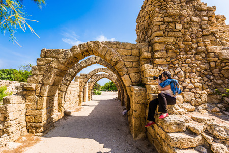 Foto de Enthusiastic woman takes pictures of the picturesque ruins of the ancient seaport of Caesarea. Excursion to the Archaeological Park in Israel. Concept of historical and phototourism - Imagen libre de derechos