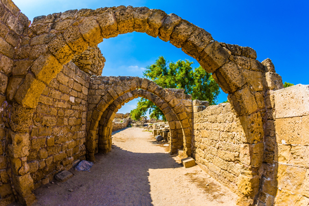 Foto de Sunny spring day. Israel.  Excursion to the Archaeological Park of the Roman Empire in ancient Caesarea. Concept of ecological and historical tourism. The remains of the covered arcades - Imagen libre de derechos