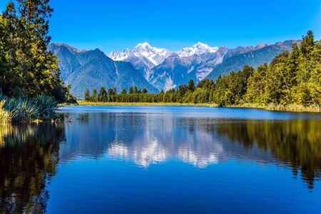 Photo pour Magnificent snow-capped mountains surround the smooth, cold waters of Lake Matheson. The forests and  Mount Cook and Mount Tasman. The concept of ecological, active and photo tourism - image libre de droit
