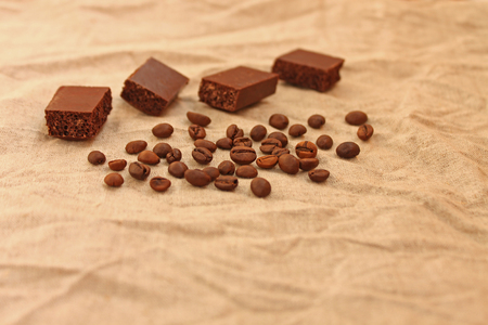 Photo for Milk porous chocolate cubes with coffee beans on a linen texture background. Sweets and coffee. Copy space. Selective focus. - Royalty Free Image