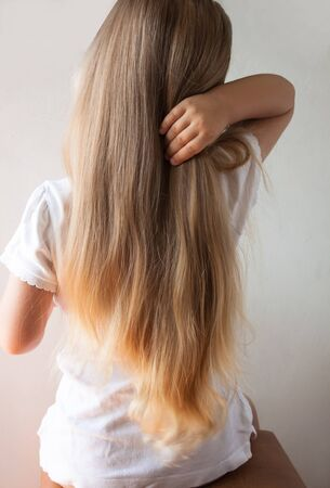 Foto de Cute girl with long blond hair. Back view of little girlie looking on side. Isolated on light background. - Imagen libre de derechos