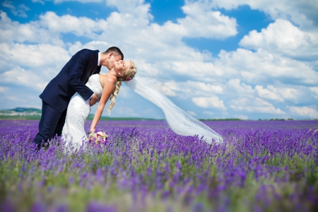 Foto de A young couple in love bride and groom, wedding day in summer  Enjoy a moment of happiness and love in a lavender field  Bride in a luxurious wedding dress on a background bright blue sky with clouds  - Imagen libre de derechos