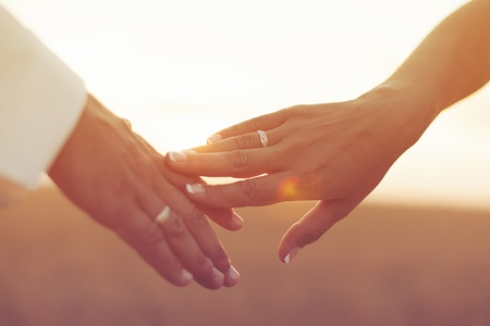 Foto de Wedding couple holding hands on sunset background - Imagen libre de derechos