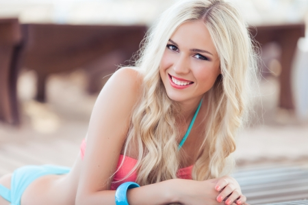 Photo pour Happy beautiful blond woman in swimsuit lying on a deckchair at the beach on vacation. - image libre de droit