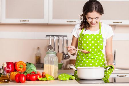 Foto de Young Woman Cooking in the kitchen. Healthy Food. Dieting Concept. Healthy Lifestyle. Cooking At Home. Prepare Food - Imagen libre de derechos