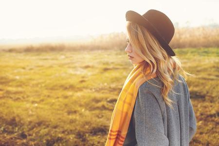 Portrait of romantic girl in a field in sunset light.