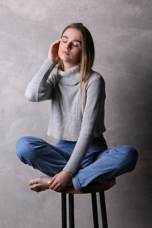 Sitting teen in pullover touching her face, girl with crossed legs, high fashion look, sitting girl, beautiful girl, blonde girl, isolated, model in studio, girl wearing jeans and sweater, long hair, gray background