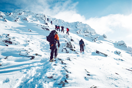 Photo pour A group of climbers ascending a mountain in winter - image libre de droit